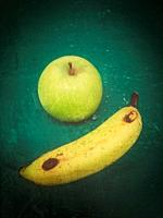 Green apple and banana on green background.