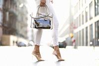 legs of stylish woman and fashionable handbag