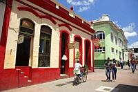 Local people walking in the street in front of the colonial buildings at the historic center, Santiago de Cuba, Cuba, West Indies, Central America