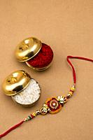 Raksha Bandhan background with an elegant Rakhi, Rice Grains and Kumkum. A traditional Indian wrist band which is a symbol of love between Brothers an...