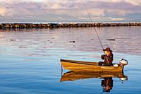 Lone fisherman in an aluminum boat at sunrise in Steveston Harbour British Columbia Canada.