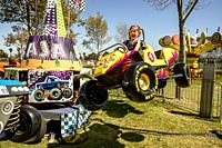 A happy four-year-old girl enjoys the car-like Baja Buggies at a Costa Mesa, CA, park.
