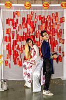 A Vietnamese American young adult couple pose in traditional Asian attire at a colorful shrine with Lunar New Year or Tet tags and signs intended to b...