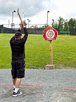 At a Whitefield, New Hampshire hotel, a man makes a swing as he aims an axe at a target on the hotel's ax-throwing range.