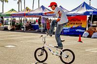 A BMX Freestyle Team biker shows careful balance in a skill demonstration in a Huntington Beach, CA, parking lot.