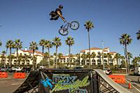 A BMX Freestyle Team biker jumps off a ramp in a skill demonstration in Huntington Beach, CA.