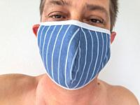 Closeup of a man wearing a face mask to protect himself from virus infection.
