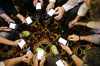 Hands of people with their smartphones working during a meeting.