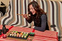 Happy lady holds a sushi roll on the chopsticks, looks at delicious Japanese food and smiles, over a table sit on a sofa, wearing cute black clothes.