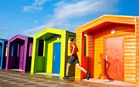Mature jogger running past beach huts at Seaton Carew on the north east coast of England. Unite Kingdom.