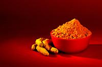 Dry Turmeric powder and roots or barks in red bowl on red background.