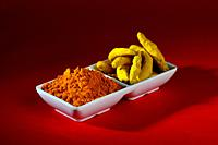 Dry Turmeric powder and roots or barks in white plate.