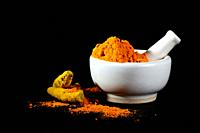 Turmeric powder in mortar with pestle and roots or barks on black background.