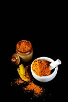 Turmeric powder in mortar with pestle and roots with clay pot on black background.