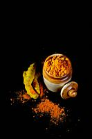 Turmeric powder in clay pot with roots or barks on black background.