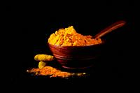 Turmeric powder and roots or sticks in wooden bowl on black background.