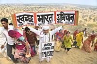 India, Rajasthan, Mukam, Samrathal Dora, ,Jambeshwar festival, Bishnoi activist holding signs among walking pilgrims against the use of plastic.