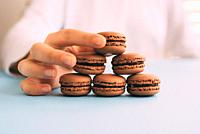 Woman placing macarons on heap on blue table. Selective focus.