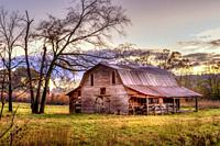 A old wooden barn in a meadow, framed by trees in the autumn.