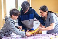mother with children prepares homemade tagliatelle pasta.
