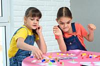 Girls play board games, one of them looks funny at the chips.