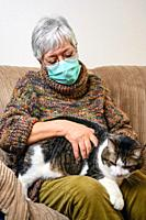 Coronavirus social distancing due to pandemic outbreak. Elderly Woman with protective face mask, Staying At Home stroking her Cat .
