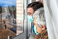 senior couple, with protective face masks, at home looking through the window. Concept of coronavirus quarantine stay home and social distancing. Lock...