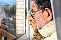 Concept of coronavirus quarantine and social distancing. Senior couple, at home looking through the window with worried expression. Stay home. Elderly...