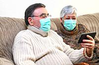 Coronavirus. Stay at home, lifestyle. Cheerful Elderly couple sitting on a sofa on a quarantine at home, making a video call with the smartphone. Seni...