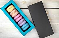 Macaroons in box next to lid on wooden background.