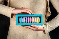 Female hands holding multicolored macaroons in gift box.
