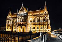 The Hungarian Parliament in Budapest on the Danube in the night lights of the street lamps.