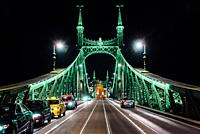 Old Iron Bridge at night in the light of streetlights across the Danube River in Budapest Hungary.