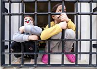 Two children look sadly outdoors through wrought-iron window. Impact on children of Covid-19 confinement.