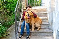 child sit on the stairs with dog - portrait of kid eleven years old and golden retriever togheter on the stairs out home.