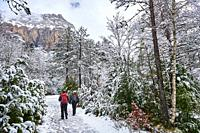 Pyrenees: Two women hiking along snowy path in the National park of Ordesa and Monte Perdido (Huesca province, Aragon region, Spain)
