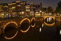Reflections of bridge lighting in canals at dusk, Amsterdam, North Holland, Netherlands.