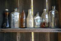 Old weathered glass bottles lined up in a row on a wood shelf - Penrose, North Carolina, USA.