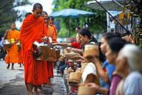 Tak bat ritual - Buddhist monks receive rice and food from pupulation in early morning in Luang Prabang , Laos, Asia.