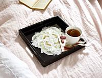 A glossy black tray holding tea sitting on a bed in the sun.