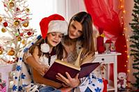 Mom and daughter sit next to a Christmas tree and read a big book.