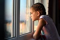 Eleven-year-old girl in isolation from boredom looks out the window.