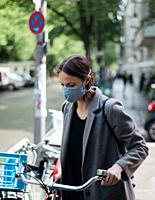 Woman with mask and bicycle.