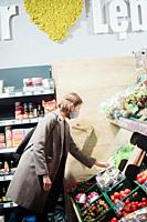 Woman in mask buying vegetables at grocery store.