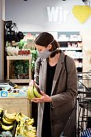 Woman in mask buying bananas at grocery store.