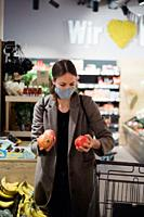 Woman in mask buying fruits at grocery store.