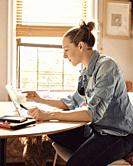 A woman working from home in her sunny kitchen, concentrating on her computer.