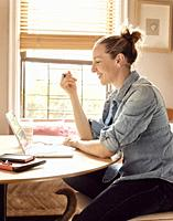 A woman working from home in her sunny kitchen, smiling at the computer.