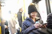 Young woman in bus, using smartphone