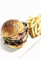 australian organic beef burger with french fries platter on white studio background.
